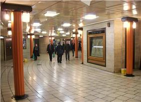 View of part of circular concourse with cream tiled floor, coffered flat ceiling and travertine stone walls. Faceted orange columns support bronze light fittings.