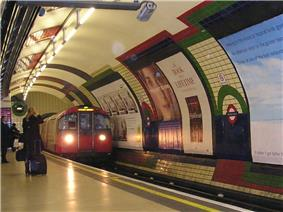 A red train running on a railway track through the interior of a building that has a rounded ceiling and rounded walls covered in advertisements