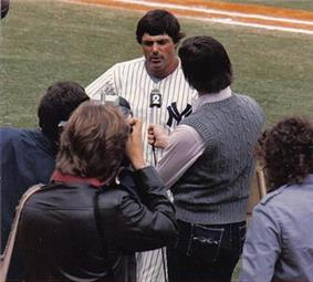 Lou Piniella, in his Yankee uniform, takes questions from the press on a baseball field
