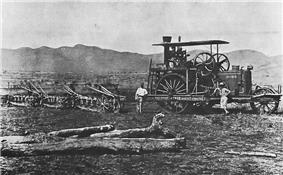 A steam-tractor in a field. Three men stand beside the machine.