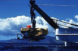A submarine, hanging from the back of a ship via a crane, is lowered into the water.