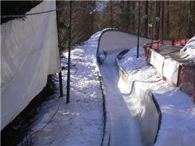 A blue sleigh in a turn of a bobsleigh run