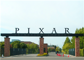 In the foreground is a paved street leading to the gate's entrance. A sign reading