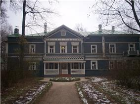 A blue two-story house with white trim and many windows, surrounded by birch trees.