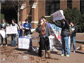A college-aged female in jacket and scarf holds the microphone attachment of a bullhorn while other students hold protest signs behind her. Two with large red X's over the words read