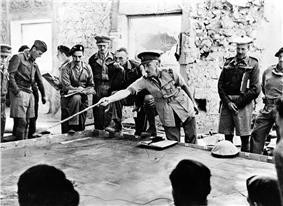 The second battle of Libya. Before zero hour. The Brigadier commanding tank units in Tobruk instructing tank commanders on the operations, using a sand table for demonstration purposes.