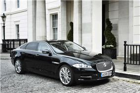 A black Jaguar XJ Sentinel parked stationary on a cobbled street in front of a white building.