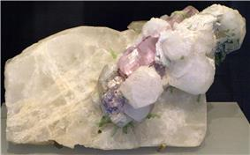A white mineral, from which white and pale pink crystals protrude