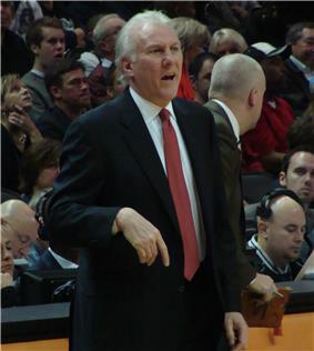 A man, wearing a black suit, white shirt and red tie, is standing in front of the spectators.