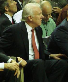 A man with white hair, wearing a black suit, white shirt and orange tie, sitting at a basketball game.