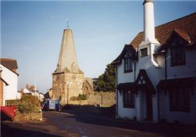 Street scene showing stone church with truncated spire, On the right is a white painted building.