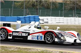 Side view of #6 white sports racing car with the words Muscle Milk on the side