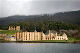 Photo of the main penitentiary building, partially ruined and hollowed out, with thickly forested hills in background