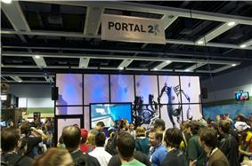 A crowd of people waiting in line in front of a partitioned 20'x20' area within a larger reception hall. The outside of the partition is decorated with Portal 2 artwork.