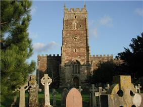 Square stone tower behind churchyard with cross and gravestones.