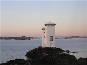 A white building consisting of a single white tower four stories high and an adjacent tower appearing to be a single storey lower, sits on a rock overlooking the sea. The sun is not visible but is evidently low in the sky as pinkish light suffuses the landcape. In the distance there are a myriad low rocky islets.