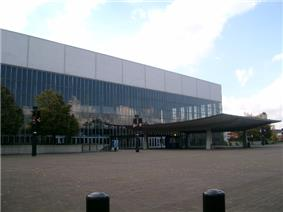 One side of a building mostly of glass windows, with a covered entrance extending to a brick plaza. Two trees grow alongside the building, and a partly cloudy sky appears in the background.