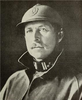 A man wearing a military uniform, and helmet, with a moustache.