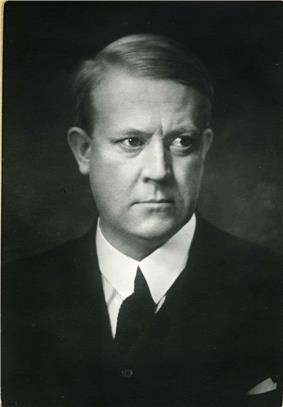 A black and white photographic portrait of a man aged around thirty, looking slightly to his left. He is dressed in a dark suit and tie; his hair is neatly combed into a parting.