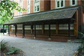 A long dark wooden structure. On the wall of the wooden structure, parallel rows of pale tiles are visible.