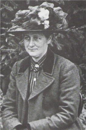 Black and white photograph dated 1912 of a middle-aged Beatrix Potter wearing a flowered hat turned slightly to her right and looking away from the photographer