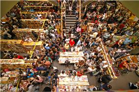 There are many people in a close proximity in a bookstore buying