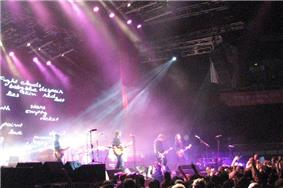 A wide shot of a stage with only four musicians visible: each is playing a type of guitar. A drum kit is mid-stage but the Coghill is obscured by lighting and equipment. The audience are across the front, below stage, some have one fist raised. A photographer is centred, front of stage, another is further to the right with a camera pointing at the band, a third cameraman is at left pointing into the crowd. Behind the group on the left is a large screen which depicts various words including