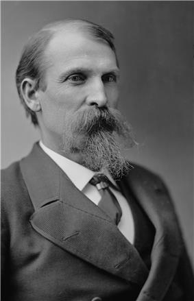 Black and white photograph of a serious-looking middle-age man with thinning hair, long mustache, and pointy beard, wearing a double-breasted waistcoat and necktie