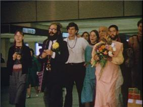Allen Ginsberg accompanies the saffron-clad swami and a group of young followers in the airport lounge