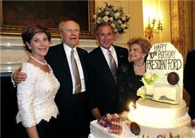Two men in suits are flanked by two women in formal dresses, standing beside a large birthday cake with lit candles and flowers. The cake is decorated with the text