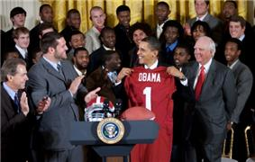 President Obama receives an Alabama jersey at the White House with various team members and coaches present.
