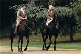 Elizabeth and Ronald Reagan on black horses. He bare-headed; she in a headscarf; both in tweeds, jodhpurs and riding boots.