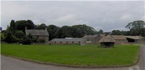 Large area of green grass with stone farm buildings behind. In the centre is a small thatched wooden building.