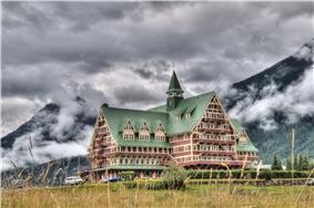 Exterior view of the Prince of Wales Hotel with the Canadian Rockies in the background