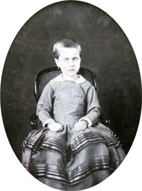 Photograph of a young Isabel with hair gathered at the back and wearing earrings seated on a small, cane back armchair