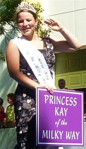 Young woman wearing sleeveless black and white print dress, smiling and waving in a parade. Sign in front of her says Princess Kay of the Milky Way