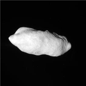An irregularly shaped oblong body is fully illuminated. It is elongated in the direction from the right to left. Its surface is covered by craters. There is valley at the top.