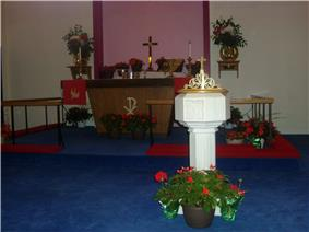A Protestant church altar and font, decorated for Pentecost with red flowering plants and green birch branches