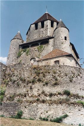 A grey stone castle rises above a stone retaining wall. The central, octagonal tower is flanked by two round towers.