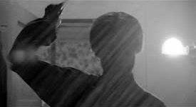 A silhouetted figure brandishes a knife towards the camera