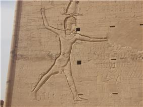 Ptolemy XII smashing his enemies with a royal mace.  Relief from the first pylon in the temple at Edfu