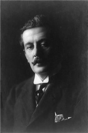 Head and shoulders portrait in heavy shadow, depicting a dark-haired man with a curling moustache, wearing a winged collar with a tie and with a handkerchief protruding from the top pocket