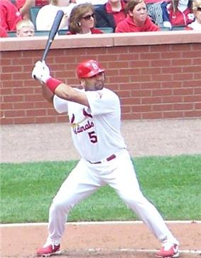 A man with feet spread apart holding a baseball bat in the air