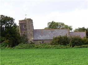 Low building with tiled roof and non-vertical square tower, surrounded by trees and with grass in the foreground.