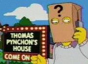 Cartoon frame showing a man with a paper bag over his head talking into a mobile phone. The bag has a large question mark printed on it and the man stands in front of a large illuminated sign in block letters which says 'THOMAS PYNCHON'S HOUSE– COME ON IN'