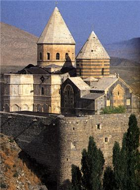 Stone church in the mountains with two massive towers topped by a conical roof