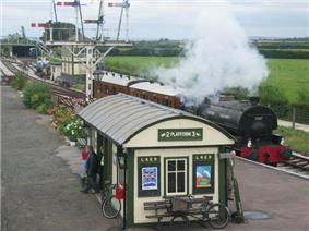 Steam locomotive at a curving station platform. On the platform is a small building with a curved roof.