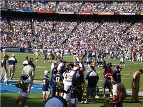 Full stands, both teams on the field, cheerleaders and lots of people milling around