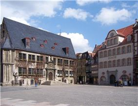 A town square with two visible buildings and a few tourists.