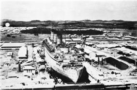 A massive ocean liner, viewed from aft and above, sits in a dry dock.
